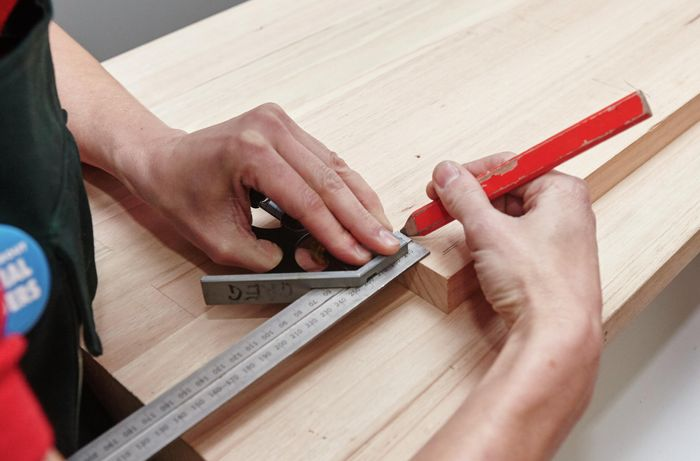 A person marking a piece of timber using a set square and pencil
