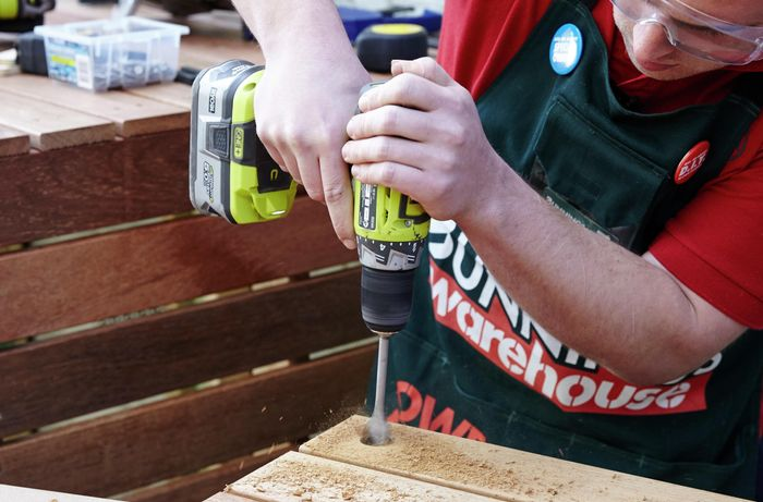 Person drilling a hole in timber.