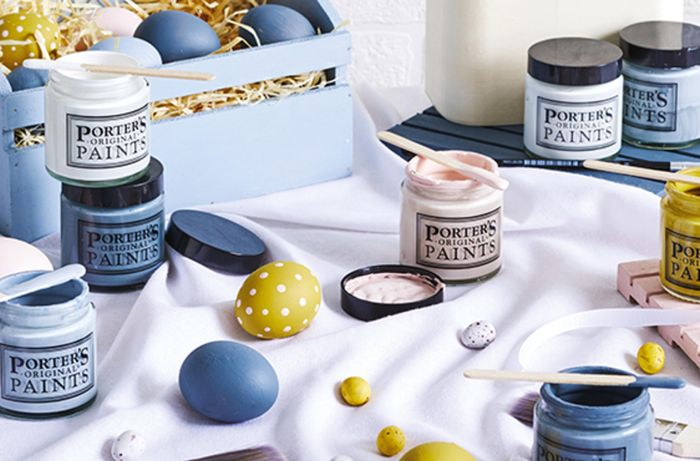 Painted eggs and paint tubs on a silk sheet
