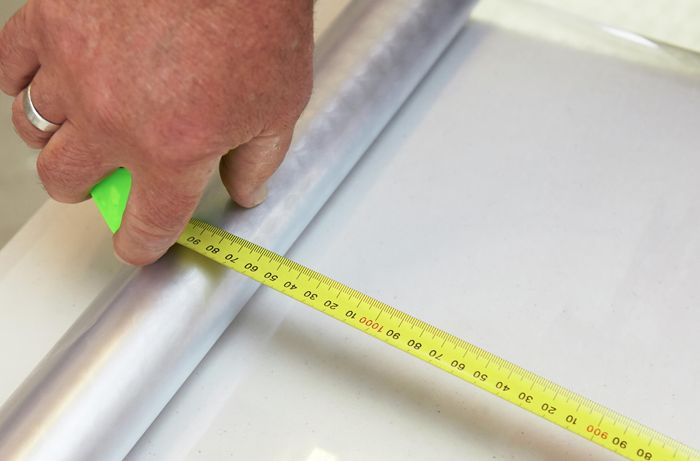 A person measuring a frosting sheet using a measuring tape