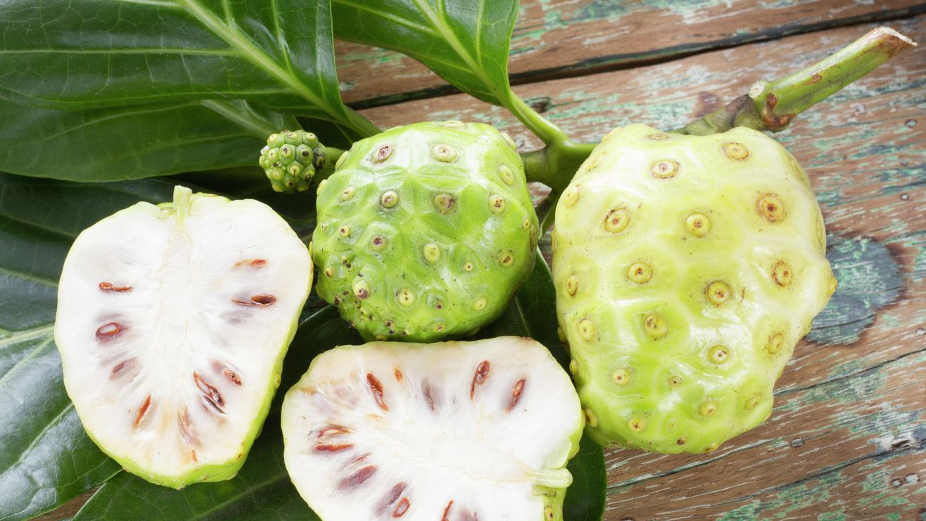 Noni fruit, some cut in half, on an outdoor table