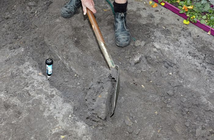 A person back-filling a trench around a pop-up sprinkler