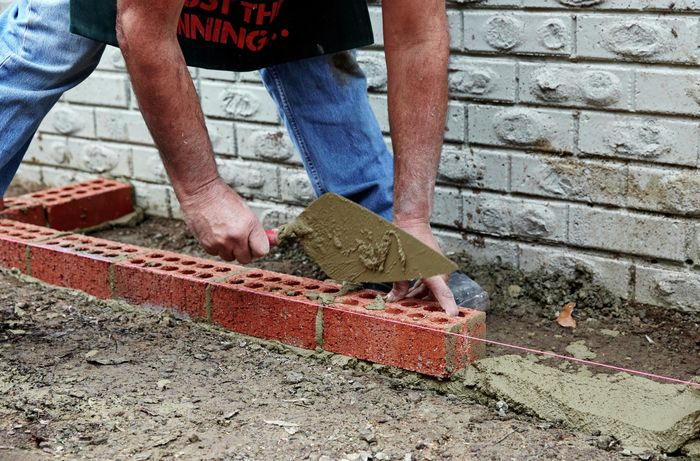 A person laying a row of bricks parallel to  a house wall following a string line