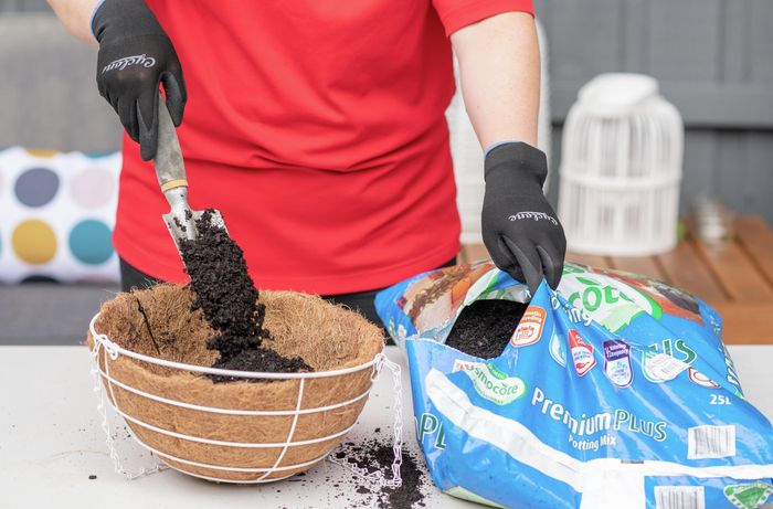 A Bunnings team member filling a hanging basket with potting mix