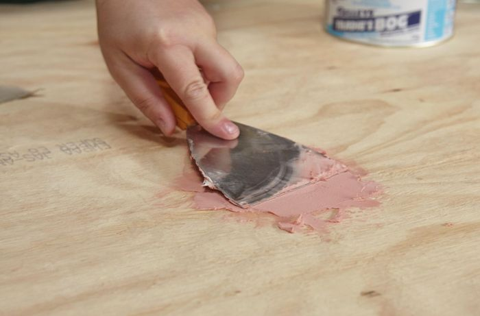 A person filling a hole in plywood using builders bog and a metal scraper
