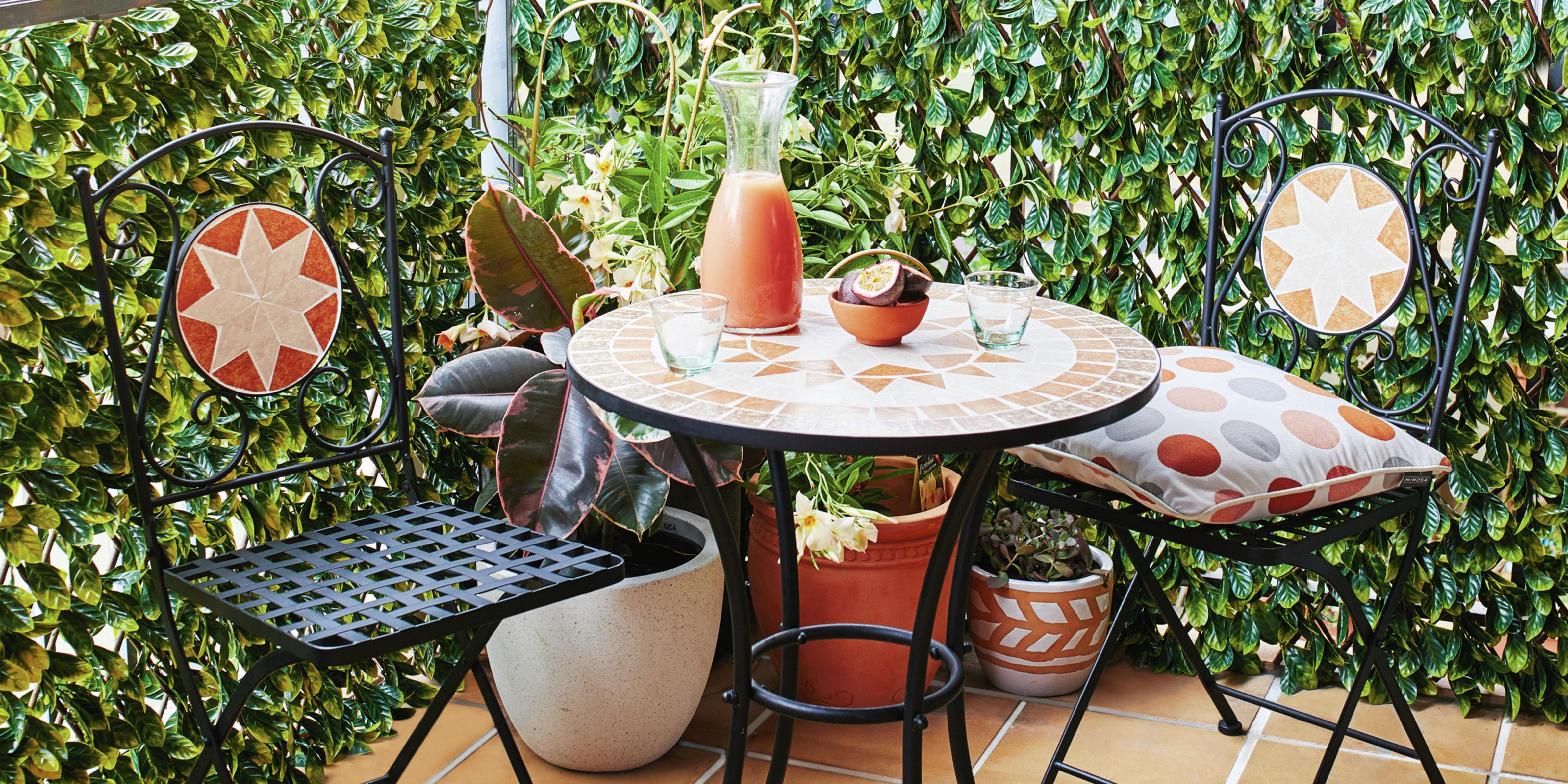 Outdoor sitting area with small table and two chairs surrounded by potted plants