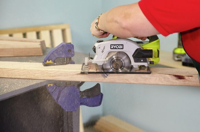 Person cutting timber bed leg with circular saw