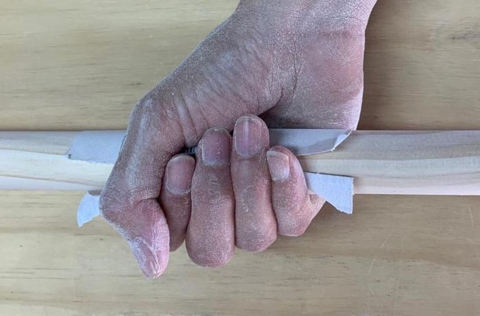 Sanding a length of timber in preparation for varnishing