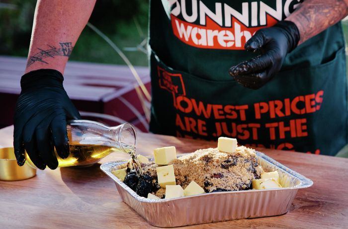 Person pouring apple juice over pork shoulder with butter cubes in cooking tray