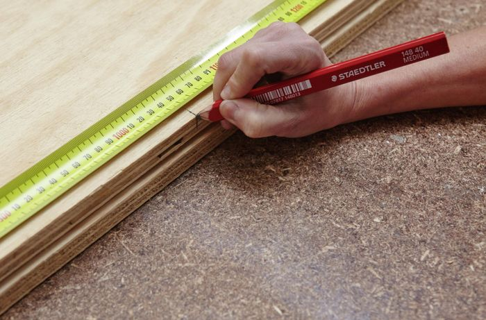 A person using a measuring tape to mark a measurement on a sheet of plywood