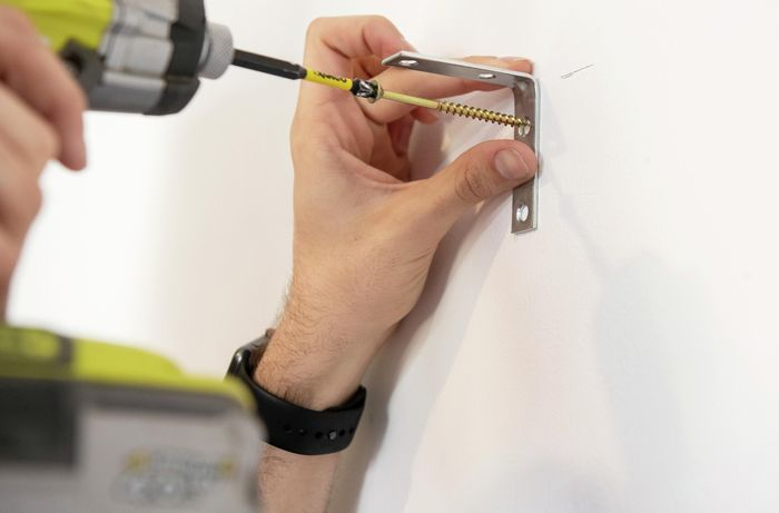 Brackets for a wall mounted cube shelf being screwed into the wall with a power drill