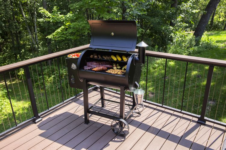 A Pit Boss grill with various cooked food in situ on a deck