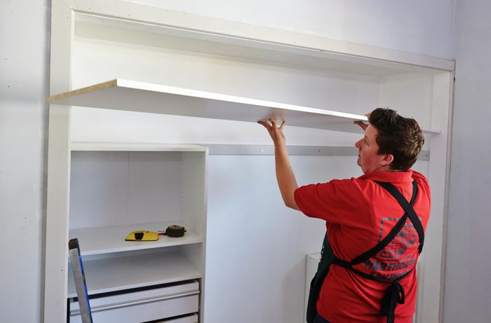 Person placing top shelf on top of wardrobe unit.
