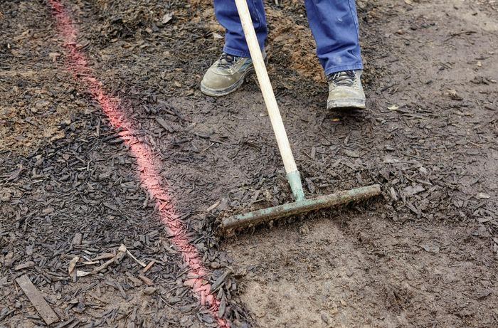 Person raking the ground next to a pink spray line