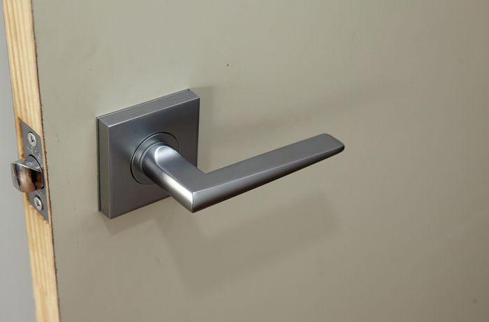 A fully installed rectangular door handle set into a door
