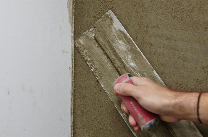 A person running a trowel towards the corner of a plastered wall