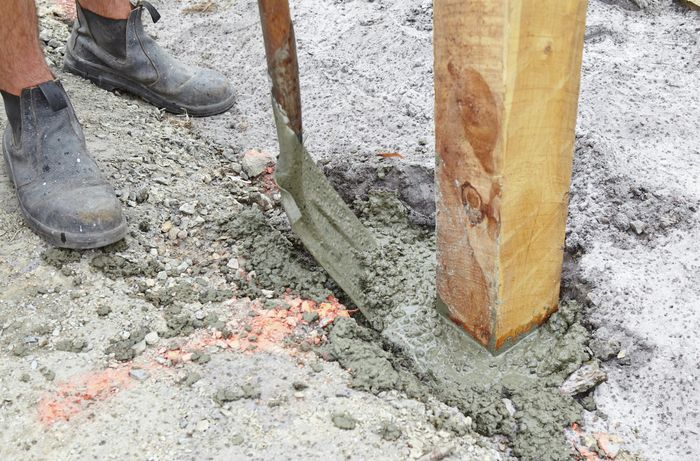 A posthole with a post positioned in it being filled with concrete