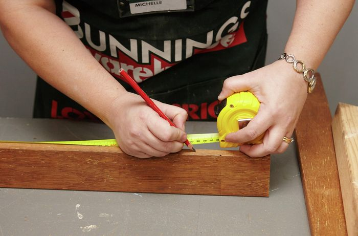 Person using measuring tape to measure side of pine frame.