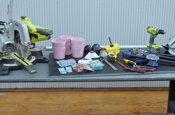 The tools and materials necessary for the job, including a mitre saw, hole saw, power drill, flowerpots, screws, chain, clamps, square rule, pliers and more