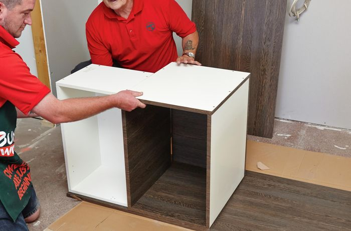 Two people positioning two cabinet units on a side panel