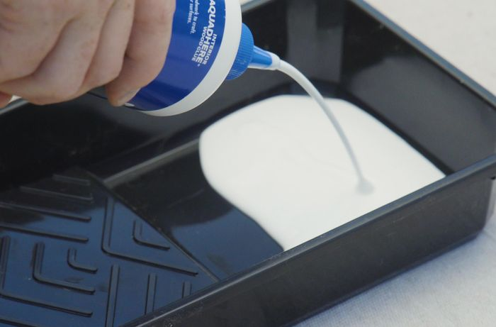 Person pouring wood glue into a paint tray