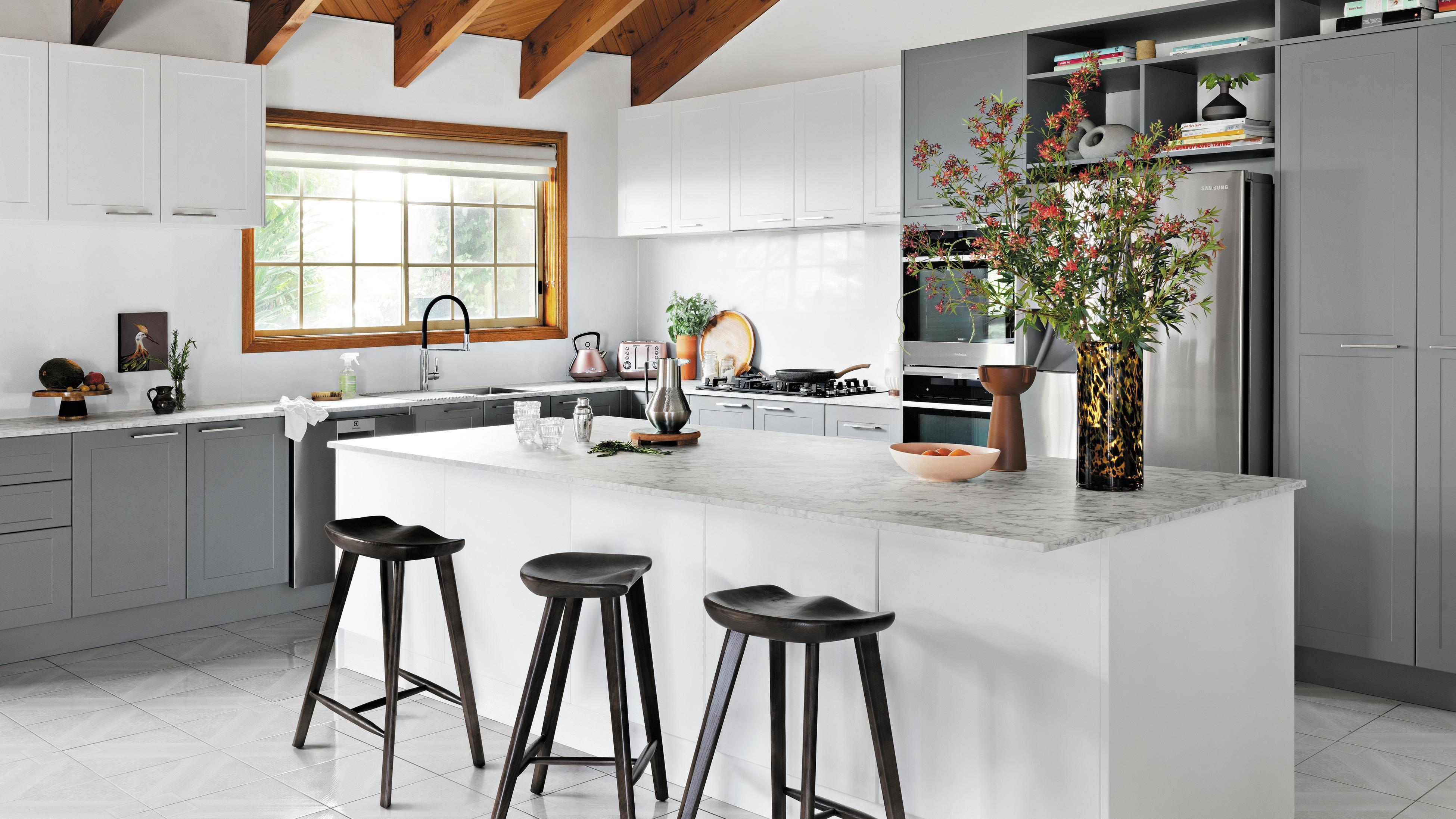 Kitchen with white and grey cabinets, a marble benchtop and a timber ceiling.