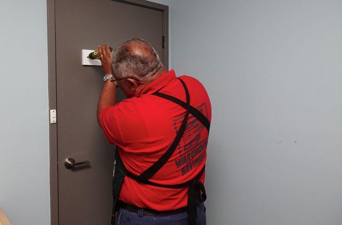 Person drilling coat rack to door