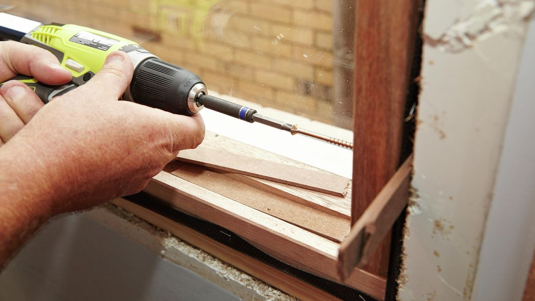 Driving screws through the pilot holes and into the frame of the house