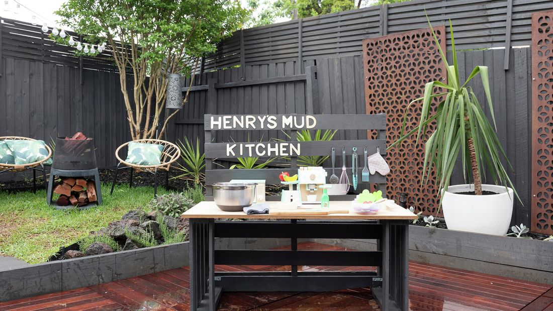 A play kitchen on a deck in a small backyard with Henry's Mud Kitchen signage