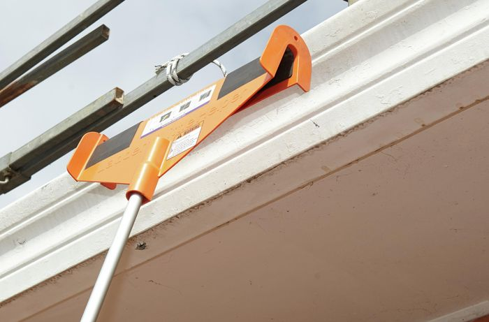A ladder's little helper leaning against a roof gutter