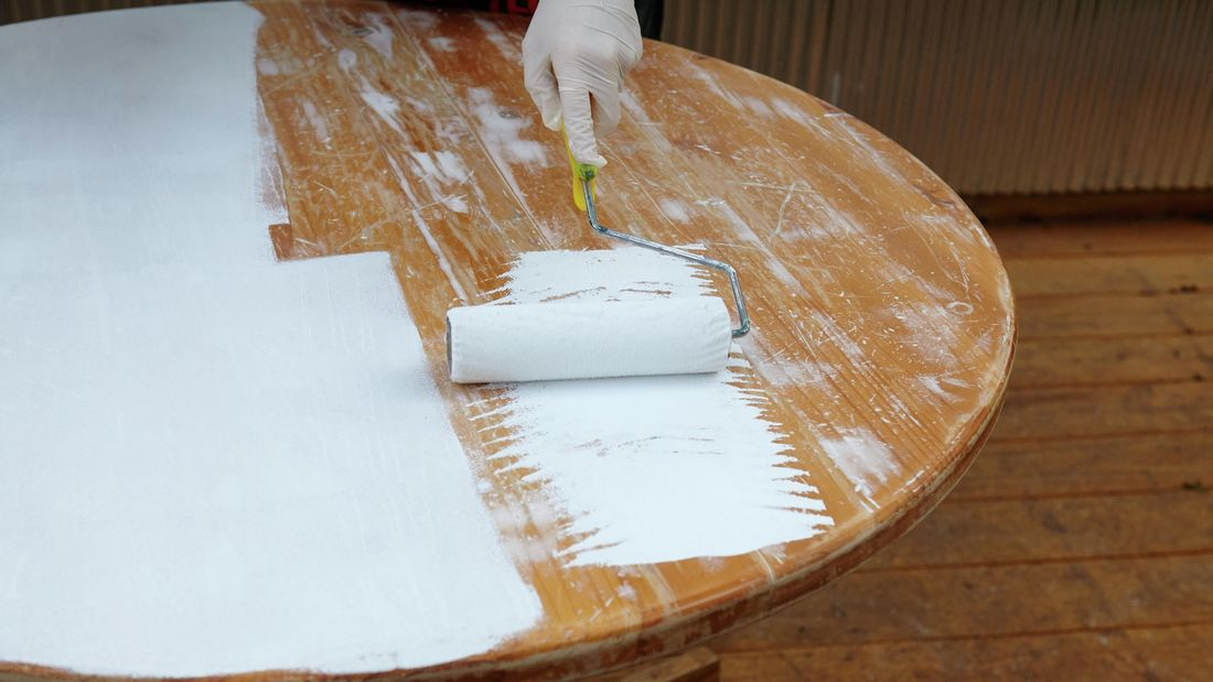 A varnished table being undercoated with a paint roller