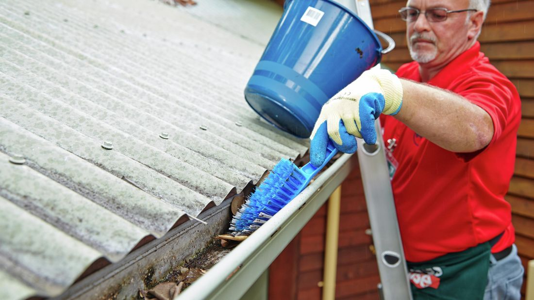 A Bunnings team member on a ladder, clearing roof guttering of leaves and other debris