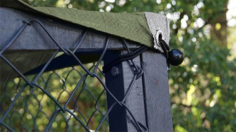 A tarpaulin secured over a wire fence