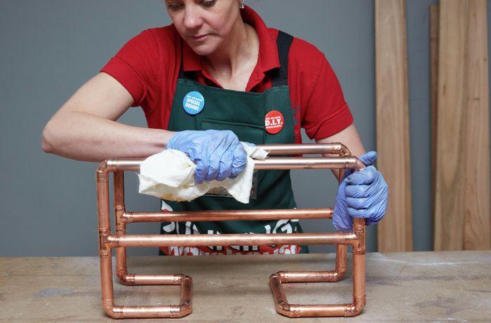 Person polishing copper magazine rack