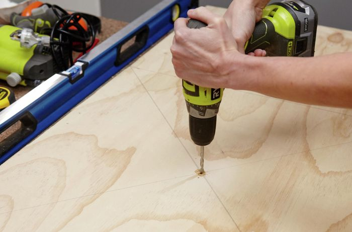 A person drilling a hole through the centre of a panel of plywood