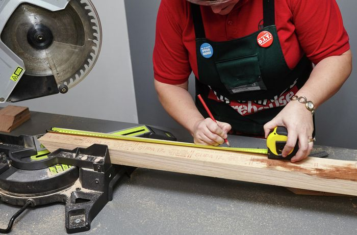 A tape measure and pencil being used to mark a length of wood
