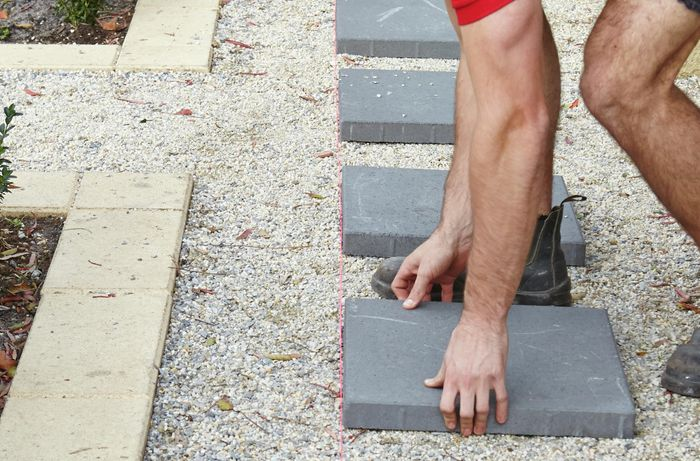 A person placing a paver along a string line on a gravel path
