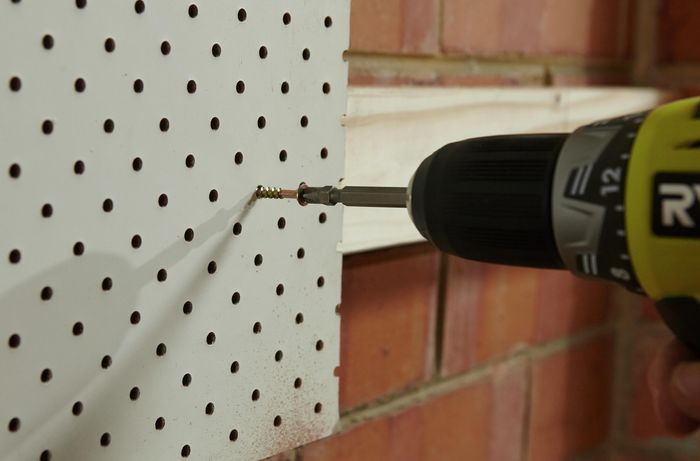 A pegboard being screwed to a mounted wooden length on a brick wall