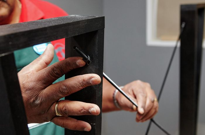 A person fitting threaded rod through table legs