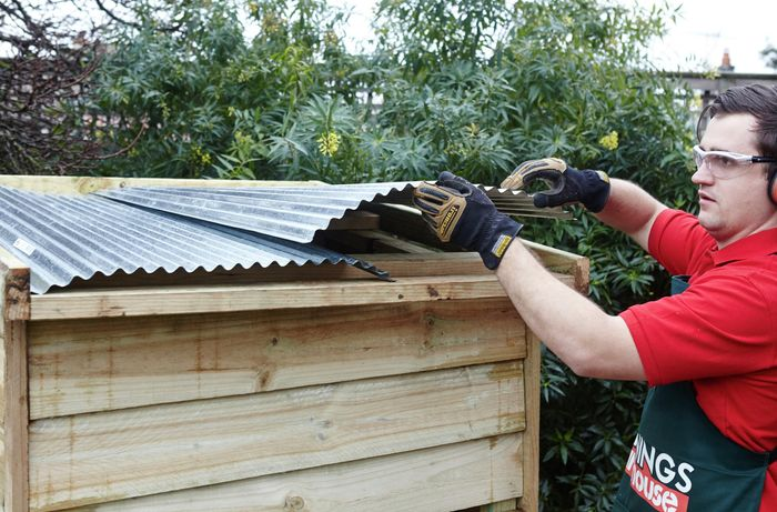 Corrugated iron being laid out over a roof frame by a Bunnings team member