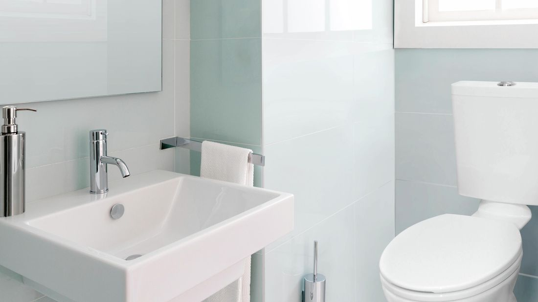 Spotless and clean toilet and sink in a modern bathroom.