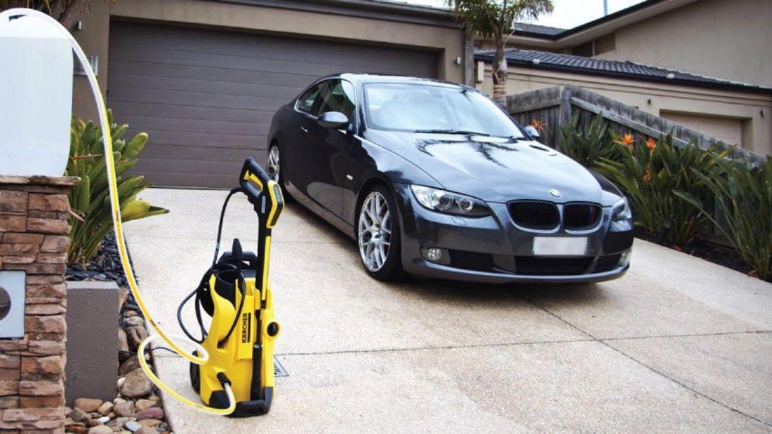 BMW sedan sitting in a driveway next to a Karcher Pressure Washer
