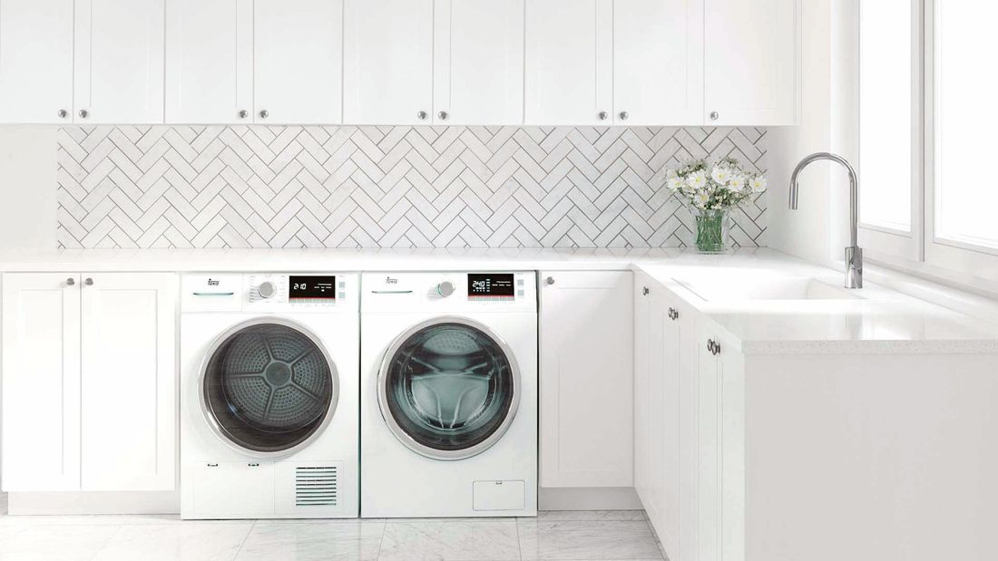 Laundry with white cabinets, white herringbone tiles and washer and dryer.