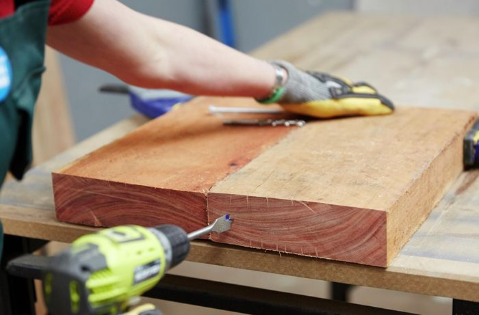 A person drilling a hole in  the end of a piece of timber