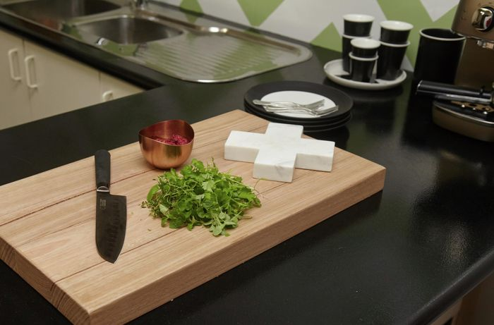 A wooden chopping board with knife and parsley