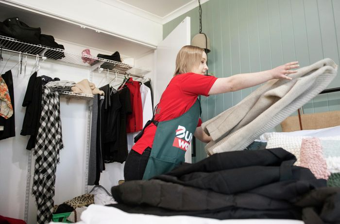 A person clearing clothes out of a bedroom wardrobe