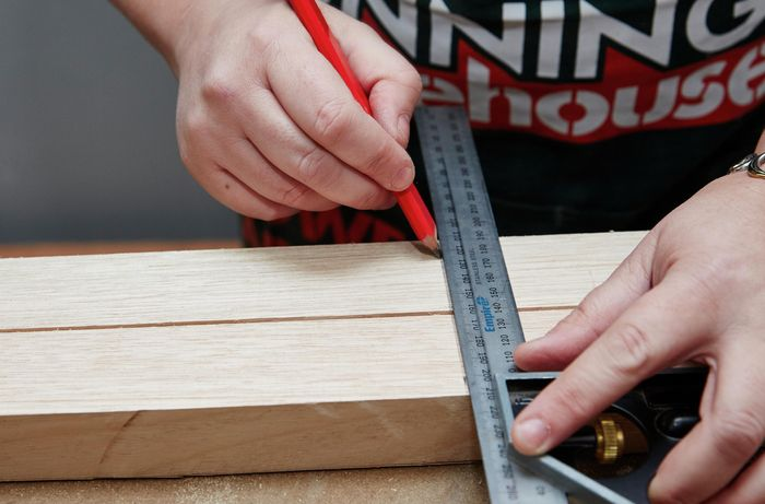 Person using a metal ruler and pencil to mark up two bits of timber.