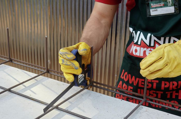 A Bunnings team member using clamps to keep two sheets of wire mesh close together for welding