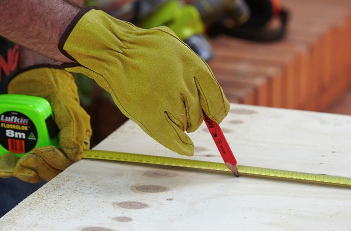 Using a pencil to mark the dimensions of the window frame