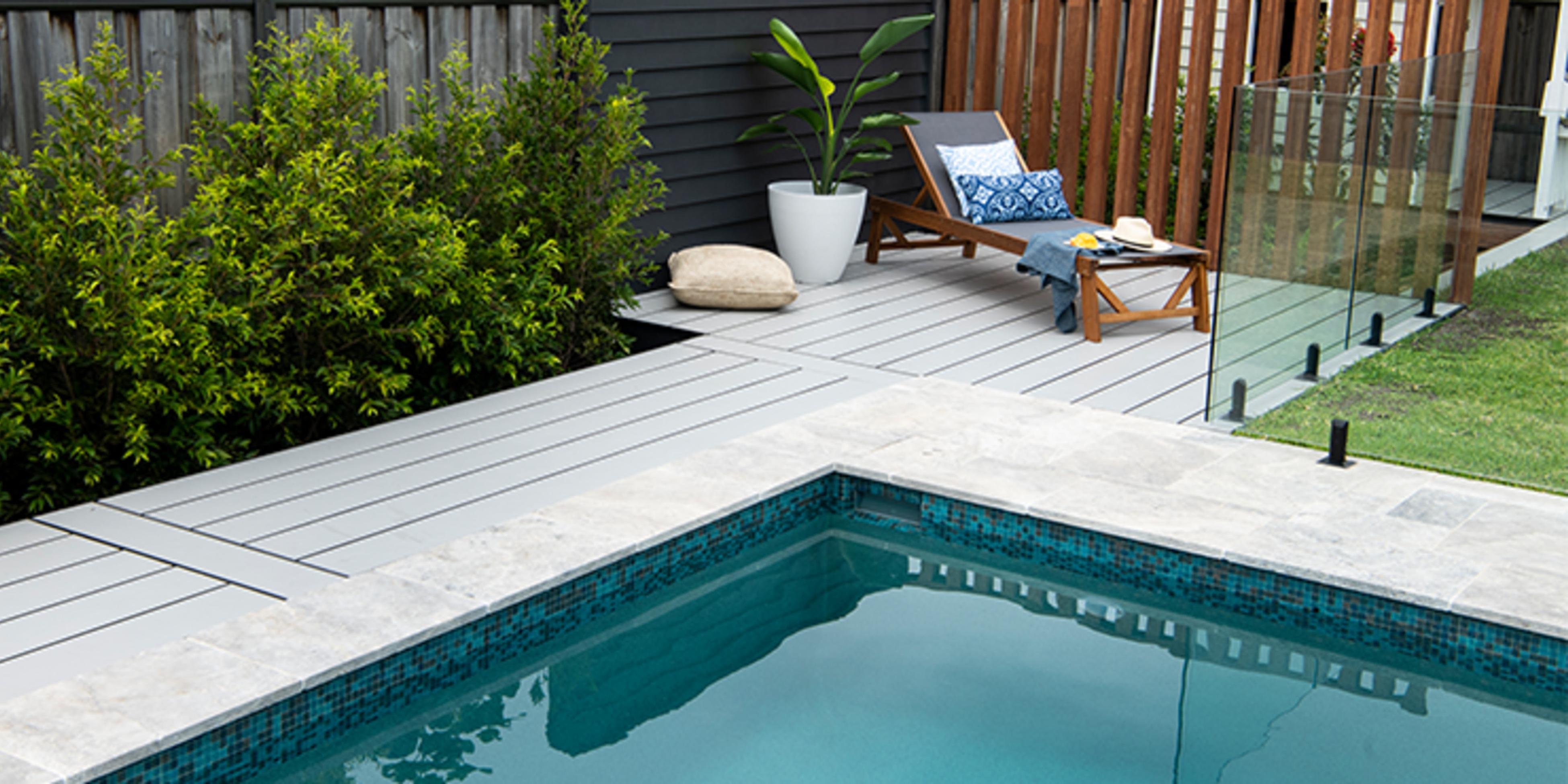 Pool surrounded by timber decking with a lounge chair